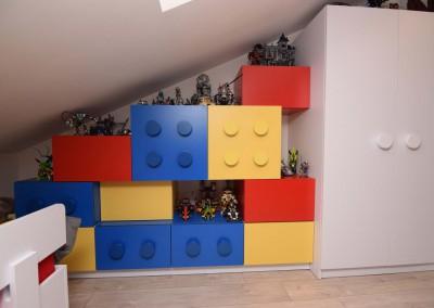 Dekoracyjny regał na ścianie pokoju dziecięcego stworzonego przez architekta z Mobiliani Design.