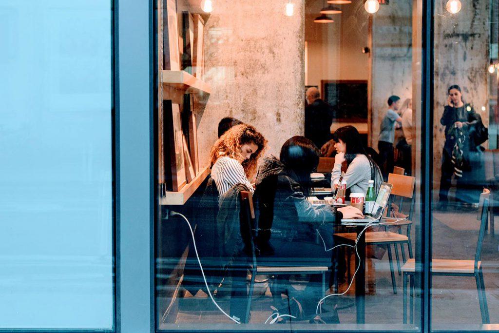 Widok z okna na wnętrza urządzonej restauracji.