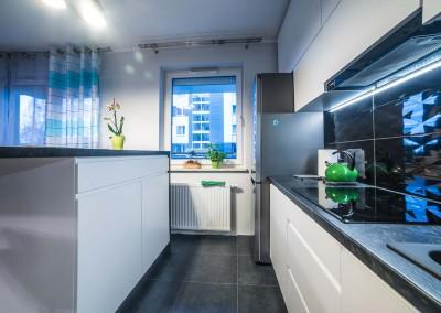 Przestrzeń kuchni między zabudową a barem.