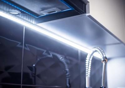 Dodatkowe podświetlenie kuchni dodające wnętrzu nowoczesnego charakteru.