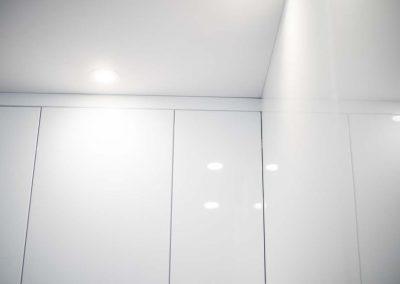 Górne szafki kuchenne w białej kuchni.
